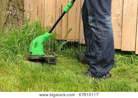 Man cutting the grass with electric trimmer