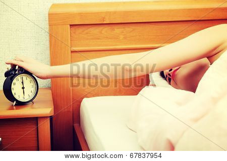 Woman is sleeping, alarm clock on table. In home.