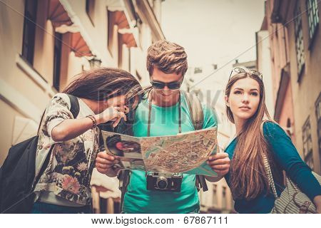 Multi ethnic friends tourists with map in old city