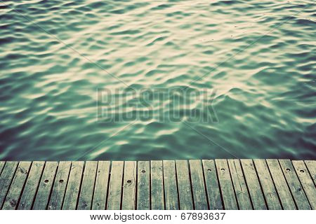 Grunge wood boards of a pier over ocean with rippling waves. Vintage background