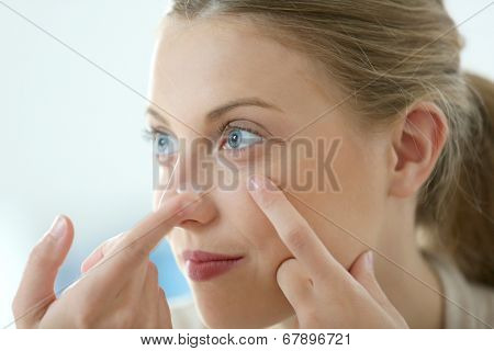 Young woman putting eye contact lense on