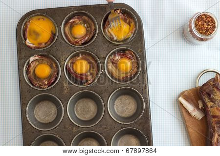 Raw Bacon And Eggs In A Muffin Pan