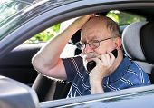 Frustrated elderly man on cell phone calls for help from his car. Closeup of man in driver's seat. poster