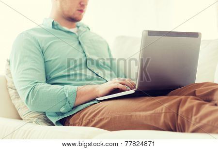 technology, home and lifestyle concept - close up of man working with laptop computer and sitting on sofa at home