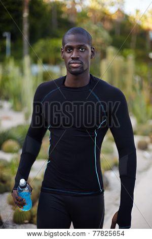 Runner resting after workout holding bottle of energy drink