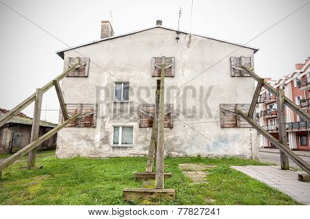 Wooden construction preventing building wall from collapsing. poster
