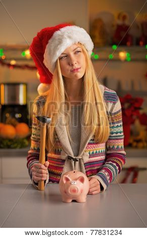 Portrait Of Thoughtful Teenager Girl In Santa Hat With Piggy Ban