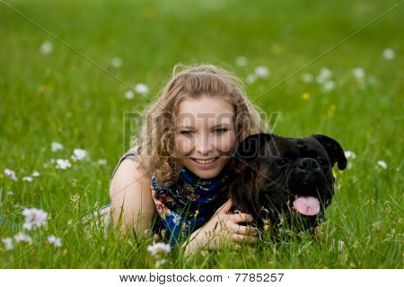 Young caucasian girl lay in the grass in park with boxer dog poster