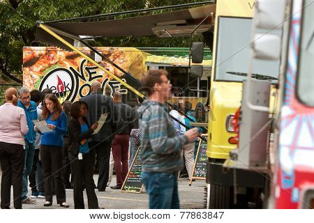 People Wait In Line To Buy Meals From Food Trucks