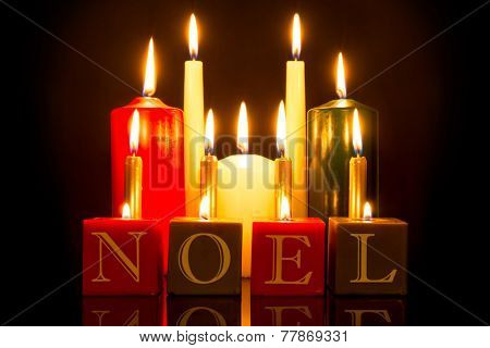 NOEL candles against a black background.
