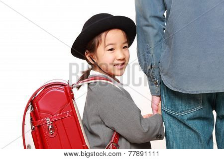 school girl with satchel walking to school with her father