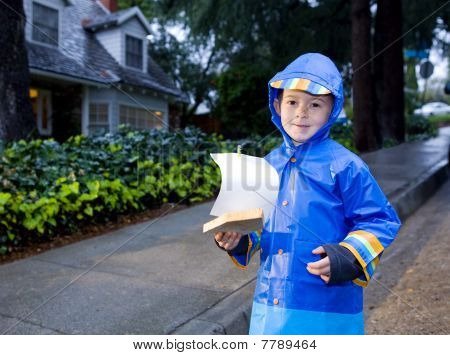 Young Boy Playing With Toy Boat In The Rain 2