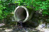 The concrete circular run-off pipe discharging water poster