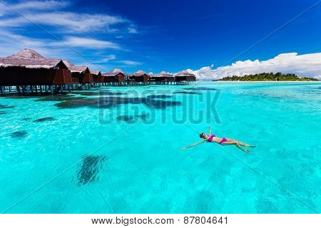 Young woman swimming from hut in blue tropical lagoon