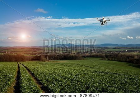 Small drone is flying above the large green field poster