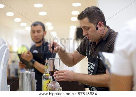 DNEPROPETROVSK, UKRAINE - JUNE 1, 2013: Barista Vitaly Panchenko makes the beverage during 5th Ukrainian Coffee In Good Spirits Championship in Dnepropetrovsk, Ukraine on June 1, 2013
