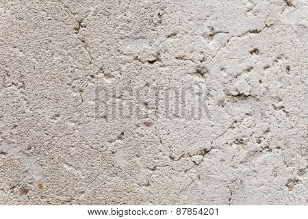 Close up on opened-up cracks in the weathered plaster of an ancient exterior wall. Rough porous stone surface with aging patina. Beige and gray color with rust brown freckles. Texture for background. poster