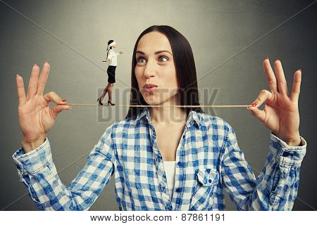 amazed woman looking at small walking woman with blindfold on the rope. photo on dark background
