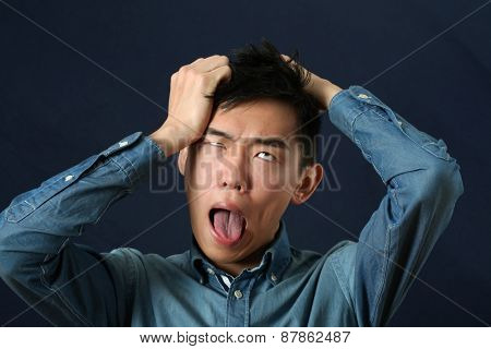 Disappointed young Asian man making face and rolling eyes up