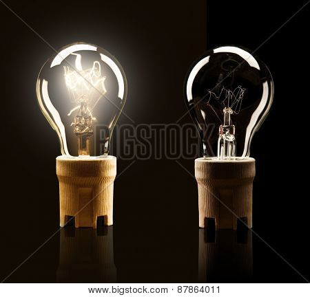 Light bulbs switched on and off, isolated on black background