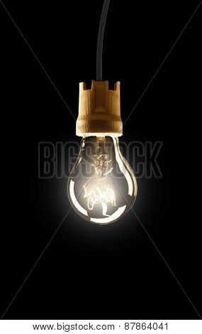 Light bulb hanging on wire, isolated on black background