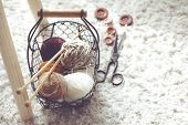 Vintage knitting needles, scissors and yarn inside old wire basket on wooden stool, still life photo with soft focus poster