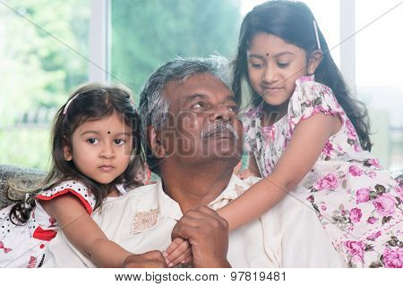 Happy Indian family at home. Asian grandfather and granddaughters playing together. Grandparent and grandchildren indoor lifestyle.