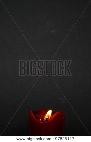 abstract old red candle with glimmer light flame on nice grey background, with blank upper space