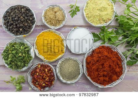 Set Of Various Spices In Shiny Bowls On A Purple Colored Wooden Table
