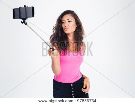 Portrait of a cute beautiful woman making selfie photo on smartphone with stick isolated on a white background