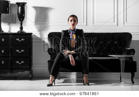 Young Beautiful Woman Sitting On Sofa In Minimalistic Inteior