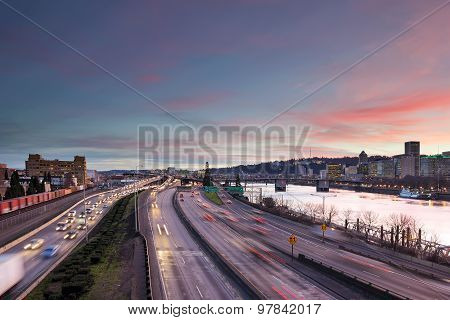 Portland Oregon rush hour traffic with city skyline along Interstate freeway during sunset evening poster