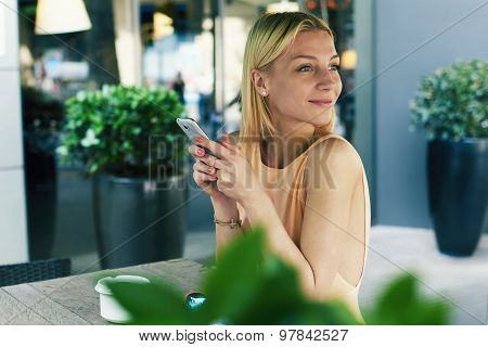 Portrait of charming young woman just read a text message on her mobile phone smiling joyfully