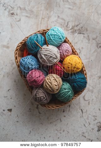 Knitting needles and yarn balls in basket poster