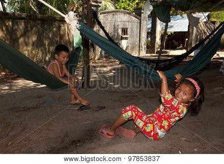 Unidentified poor cambodian children playing in hammocks
