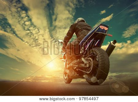 Man seat on the motorcycle under sky with clouds