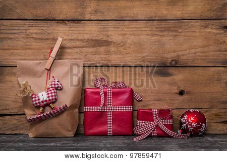 Classical red christmas gifts wrapped in paper with handmade sewed rocking horse and clothes peg. poster
