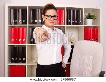 Angry usiness woman pointing at person in her office