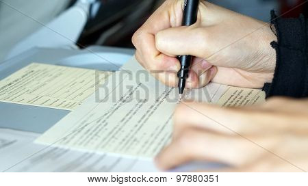 hand filling immigration form on flight to visit country poster