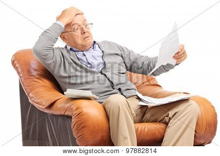 Shocked senior gentleman looking at his bills in disbelief seated in an armchair isolated on white background