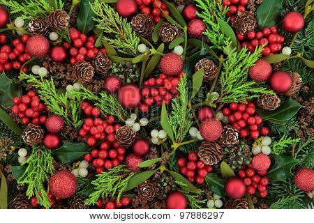 Christmas abstract background with red bauble decorations, holly, ivy, mistletoe, blue spruce fir and cedar cypress greenery.
