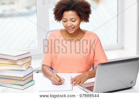 people, technology and education concept - happy african american young woman sitting at table with laptop computer and books at home