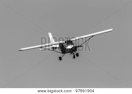 Flying light two seater prop aircraft plane in vintage black and white. poster