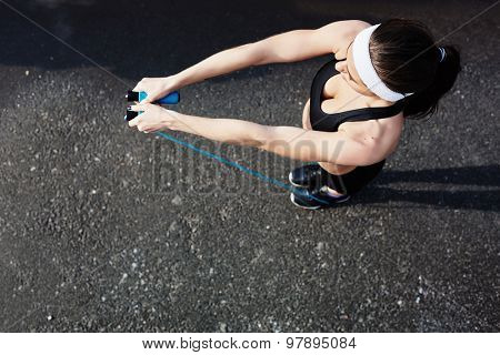 Sporty woman holding skipping-rope in stretched arms poster