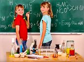 Happy child holding flask and writting on blackboard in chemistry class. poster
