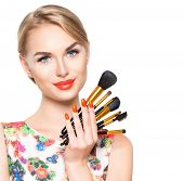 Beauty Woman with Makeup Brushes. Natural Make-up for Blonde Model Girl with Blue Eyes. Beautiful Face. Makeover. Perfect Skin. Applying Holiday Makeup with orange color lipstick and manicure poster