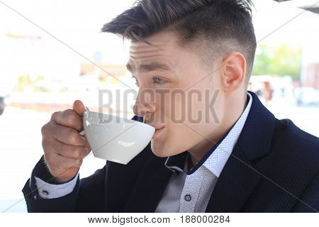Portrait of a confident businessman sitting on the bench and drinking coffee outdoors
