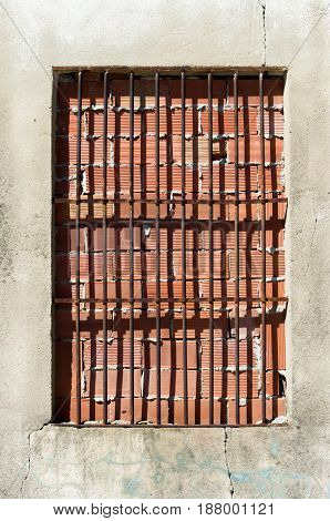 Window blocked with bricks and with bars