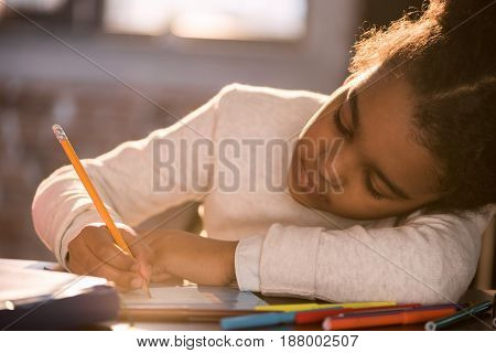 Close-up Portrait Of Adorable African American Girl Drawing With Pencil, Doing Homework Concept