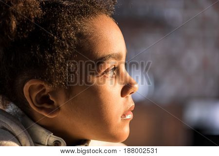 Close-up profile portrait of adorable african american girl looking away